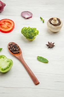 Widok z dołu świeże warzywa czarny pieprz w drewnianej łyżce grzyby czerwony pomidor cebula brokuły liście mięty na szarym stole