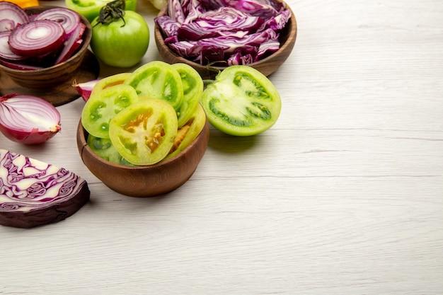 Widok z dołu świeże warzywa pokroić zielone pomidory pokroić czerwoną kapustę pokroić cebulę w miskach na białym drewnianym stole z wolną przestrzenią