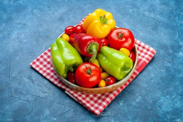 Widok z dołu świeże warzywa pomidorki koktajlowe różne kolory papryka pomidory cumcuat na talerzu na czerwono biały ręcznik kuchenny w kratkę na niebieskiej powierzchni