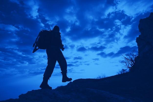 Widok z dołu sylwetka mężczyzny podróżnika z plecakiem wspina się po górach na tle błękitnego nieba w białych chmurach. pojęcie nieznanego i miłośników turystyki górskiej
