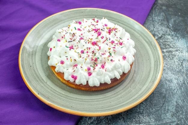 Widok z dołu tort z kremowym fioletowym szalem na szarym stole