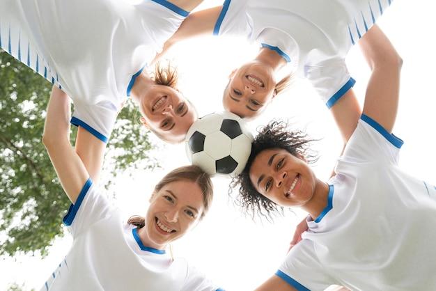 Widok z dołu uśmiechnięte kobiety trzymające piłkę