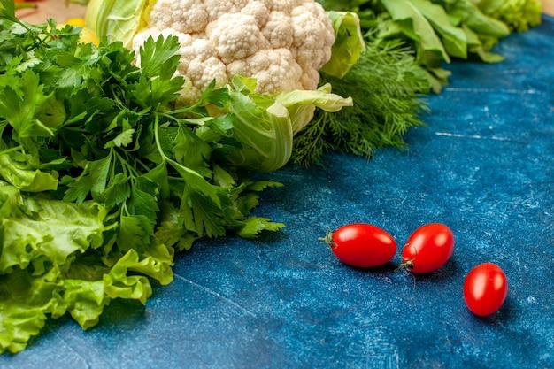 Widok z dołu warzywa pietruszka koper sałata kalafior pomidorki koktajlowe na niebieskim stole