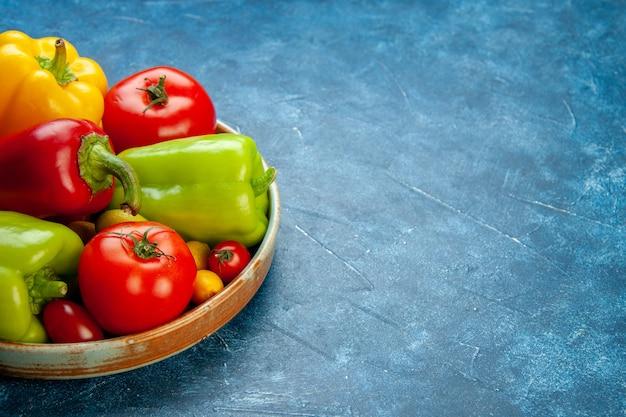 Widok z dołu warzywa różne kolory papryka pomidory pomidorki koktajlowe na drewnianym półmisku na niebieskim stole z miejscem na kopię
