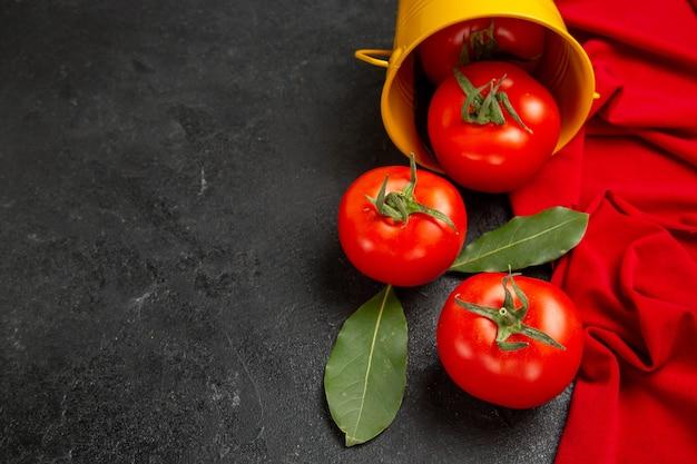Widok z dołu wiadro z czerwonymi pomidorami ręcznik na ciemnym tle