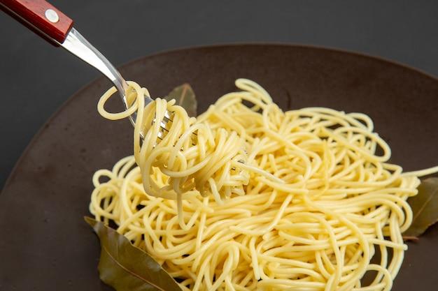 Widok z dołu widelec do makaronu spaghetti na talerzu na czarnym tle