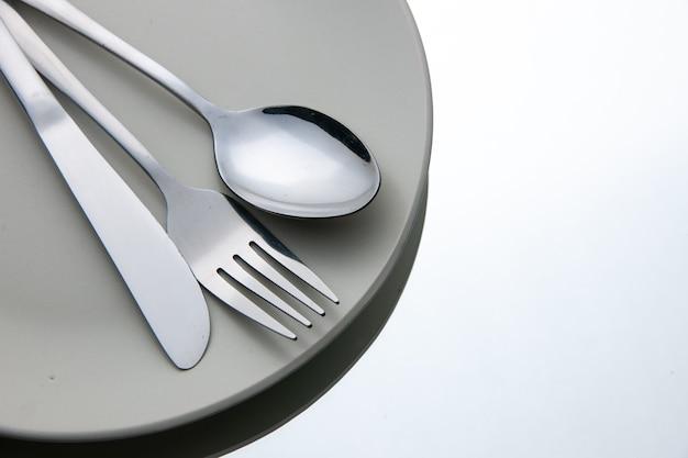 Widok z dołu widelec łyżka nóż na talerzu na białym odosobnionym miejscu kopiowania powierzchni