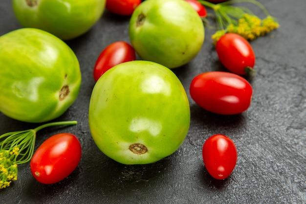 Widok z dołu z bliska zielone pomidory i pomidory czereśniowe oraz kwiaty koperku na ciemnym tle