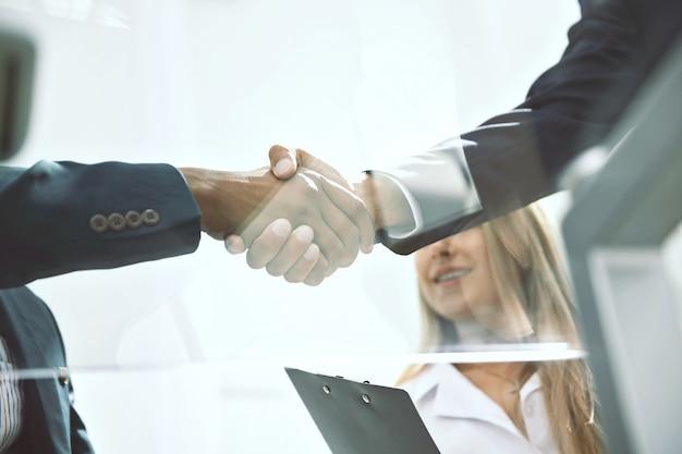 Widok z dołu. zbliżenie partnerów biznesowych uścisk dłoni. tło biznesowe