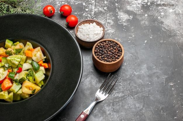 Widok z dołu zielona sałatka z pomidorów na owalnym talerzu widelec przyprawy pomidory na ciemnym tle
