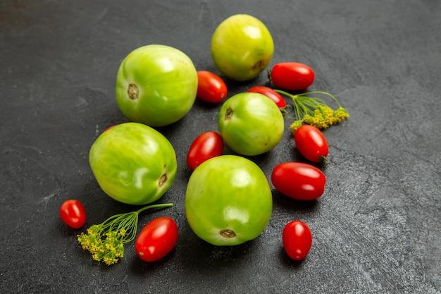 Widok z dołu zielone pomidory i pomidory czereśniowe oraz kwiaty kopru na ciemnym tle