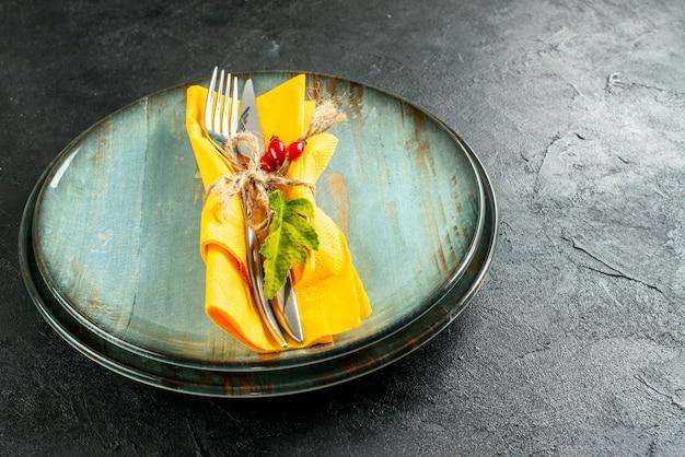 Widok z dołu żółty nóż do serwetek i widelec przywiązane liną na talerzach na czarnej ziemi