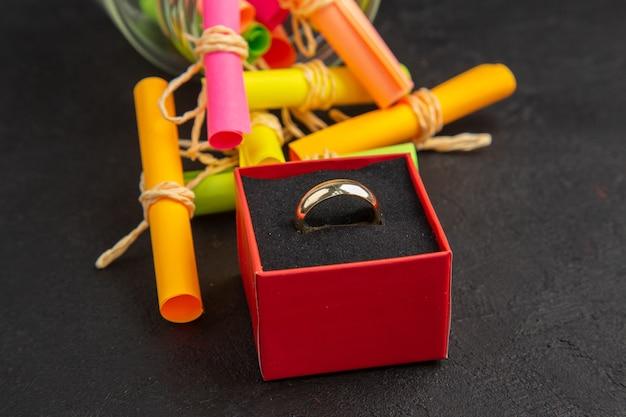 Widok z dołu zwój życzeń rozrzuconych z pierścienia słoika w pudełku na ciemnym tle