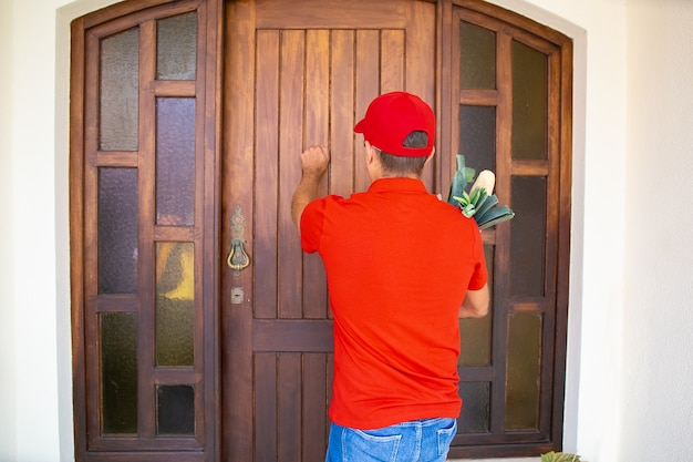Widok z dostawcy pukanie do drzwi i trzymanie żywności ze sklepu spożywczego z tyłu. doświadczony kurier w czerwonej koszuli i czapce dostarczający zamówienie do domu. dostawa żywności i koncepcja zakupów online