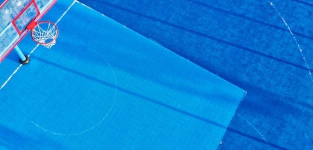 Widok z drona na boisko do koszykówki z niebieską powłoką, sztuczna murawa.