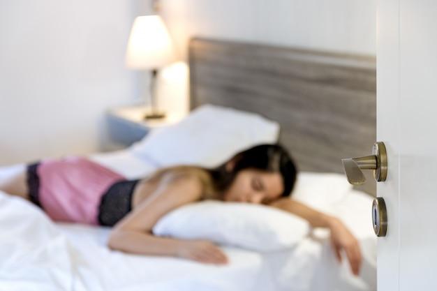 Widok z drzwi kobiety leżącej w łóżku nieostry