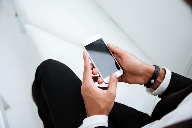 Widok z góry afrykańskiego biznesu człowieka w czarnym garniturze, trzymając telefon w rękach w biurze. przycięty obraz