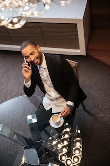 Widok z góry afrykańskiego mężczyzny w garniturze rozmawia przez telefon i siedzi przy stole z filiżanką kawy. portret pionowy