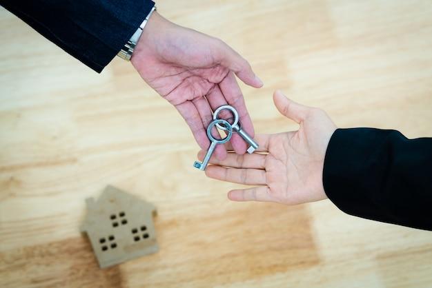 Widok z góry agent nieruchomości daje klucz do domu rodzinie po podpisaniu umowy pożyczki mieszkaniowej