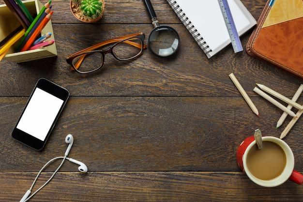 Widok z góry akcesoria biurowe telefon komórkowy, papier notatkowy, ołówek, kawa, kaktus na drewnianym biurku biurko.