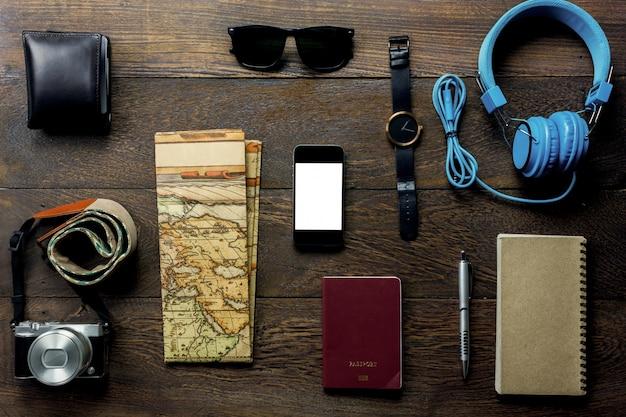 Widok z góry akcesoria podróż z telefonem komórkowym, paszportem, aparatem fotograficznym, słuchawkami, portmonetką, notatnikiem, mapą, oglądać na stole drewniane z copy space.travel koncepcji.