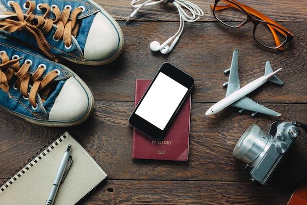 Widok z góry akcesoria podróży z telefonu komórkowego, paszportu, aparat fotograficzny, słuchawki, notatnik, szklarnie, samolot na stole drewniane z miejsca kopiowania. koncepcja podróży.