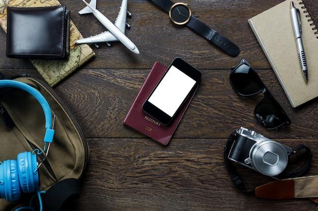 Widok z góry akcesoria podróży z telefonu komórkowego, paszportu, kamery, samolot, słuchawki, portmonetka, notatnik, mapę na stole drewniane z miejsca kopiowania. koncepcja podróży.