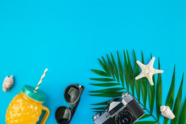Widok z góry akcesoriów podróżnych z liśćmi palmowymi