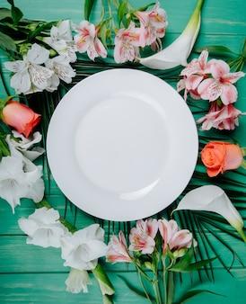 Widok z góry alstremerii w kolorze białym i koralowym oraz róż z mieczykami i liliami calla ułożonymi wokół białego talerza na zielonym drewnianym tle