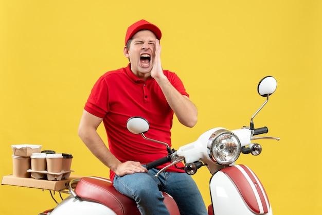 Widok z góry ambitnego emocjonalnego młodego faceta w czerwonej bluzce i kapeluszu, wykonującego zamówienia, dzwoniącego do kogoś na żółtym tle