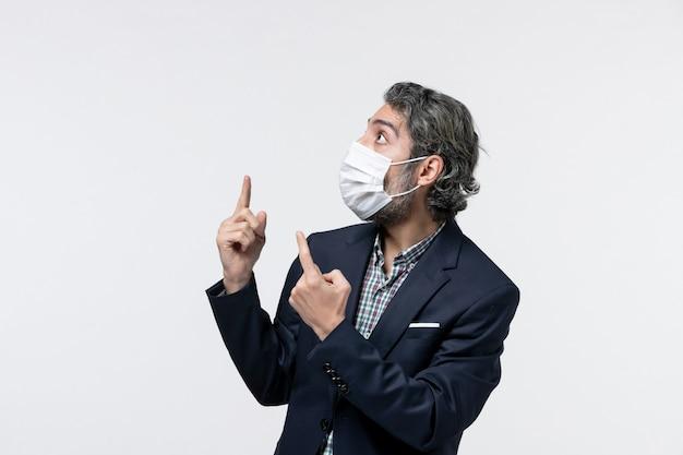 Widok z góry ambitnego młodego faceta w garniturze, noszącego maskę i wskazującego na białą powierzchnię