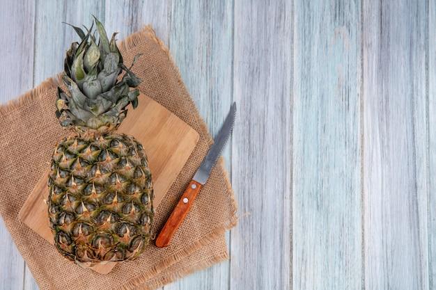 Widok z góry ananasa na desce do krojenia z nożem na worze i drewnianej powierzchni