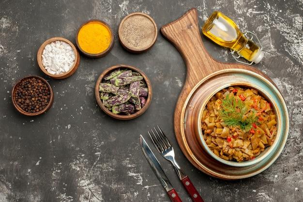 Widok z góry apetyczne danie apetyczna zielona fasolka z pomidorami na desce obok widelca noża butelka oleju i brązowe miski kolorowych przypraw na ciemnym stole