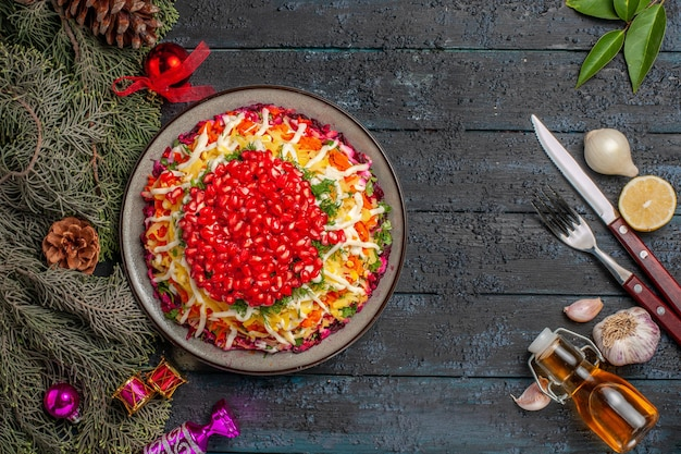 Widok z góry apetyczne danie świąteczne danie z pestkami granatu obok butelki oleju widelec nóż gałązki drzewa cytryna i czosnek