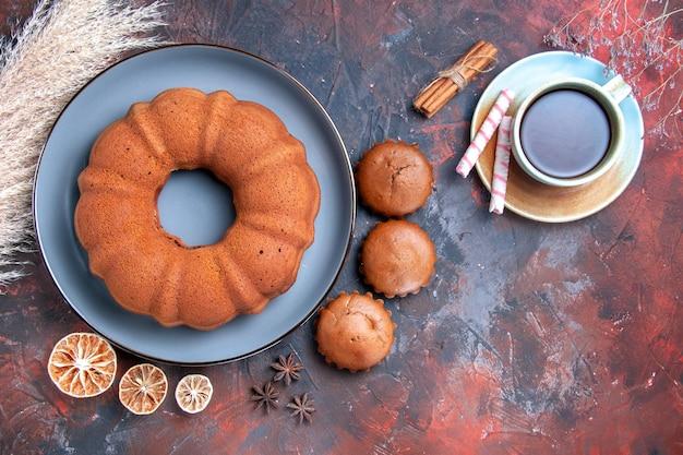 Widok z góry apetyczny tort talerz ciastek babeczki filiżanka herbaty cytryna laski cynamonu