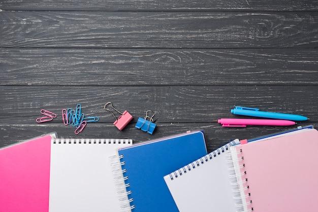 Widok z góry asortymentu na kolorowe zeszyty z długopisami i spinaczami do papieru