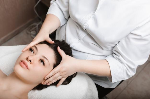 Widok z góry atrakcyjnej kobiety wykonującej pielęgnacyjny masaż twarzy, opierając się na łóżku spa z otwartymi oczami w centrum odnowy biologicznej.