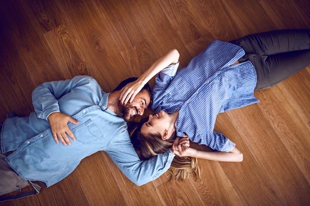 Widok z góry atrakcyjnej pary kaukaskiej w miłości, leżącej na podłodze, przytulanie i patrząc na siebie.