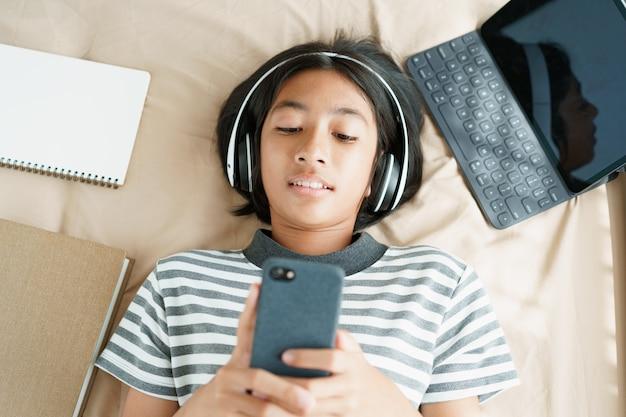Widok z góry azjatyckiej dziewczynki leży, słuchając muzyki na swoim smartfonie
