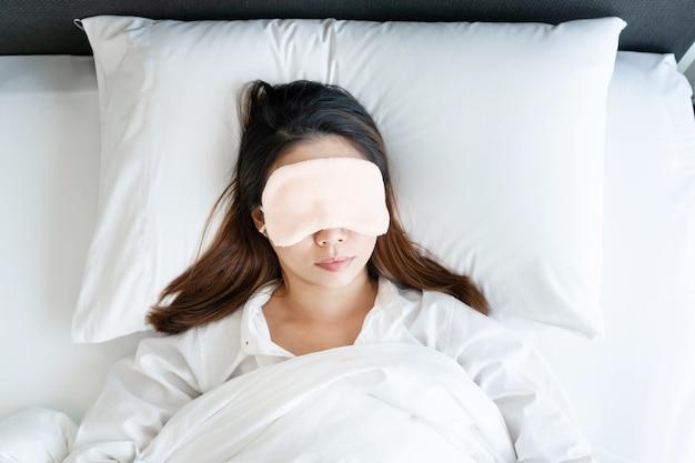 Widok z góry azjatyckiej kobiety w masce do spania śpiącej w łóżku rano.