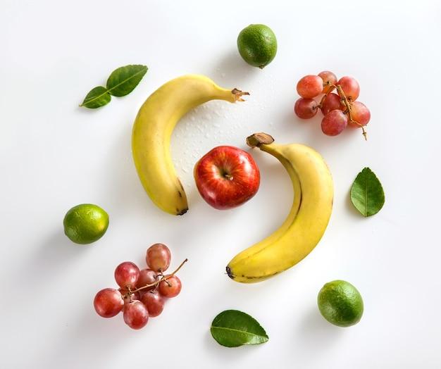 Widok z góry banan, cytryna, jabłko i winogrono z liśćmi na białym tle