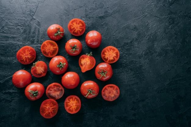 Widok z góry bardzo dojrzałych pomidorów i plasterków na ciemnym tle z bezpłatną przestrzenią.