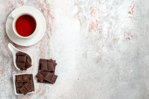 Widok z góry batoników czekoladowych z filiżanką herbaty na białej powierzchni