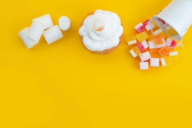Widok z góry bezy i pianki marshmallows z marmoladą na żółtym, cukrowo-cukierkowym kolorze