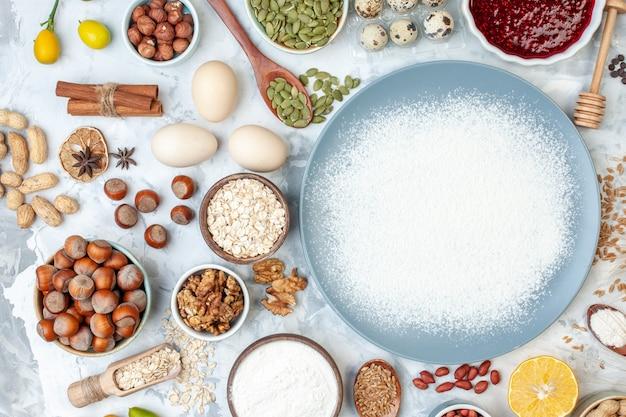 Widok z góry biała mąka wewnątrz talerza z orzechami, nasionami i jajkami na białym cieście, pieczenie galaretki orzechowej w kolorze żywności