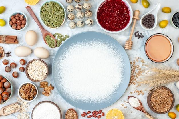 Widok z góry biała mąka wewnątrz talerza z orzechami, nasionami i jajkami na białym cieście, pieczenie żywności w kolorze galaretki orzechowej