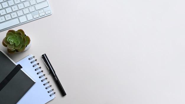 Widok z góry białe biurko z klawiaturą, notatnikiem i kaktusem.
