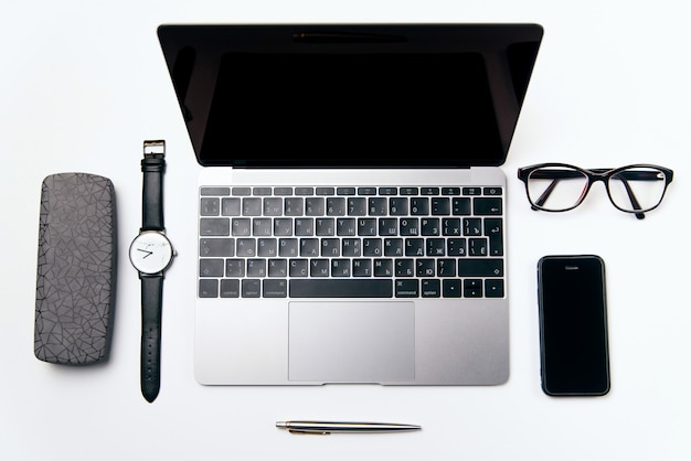 Widok z góry białe biurko z laptopem, telefonem i materiałami, leżał płasko.