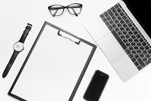 Widok z góry białe biurko z laptopem, telefonem, jasne puste miejsce na papier i materiały eksploatacyjne