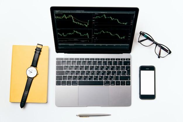 Widok z góry białe biurko z laptopem, telefonem, notatnikiem i materiałami, leżał płasko.